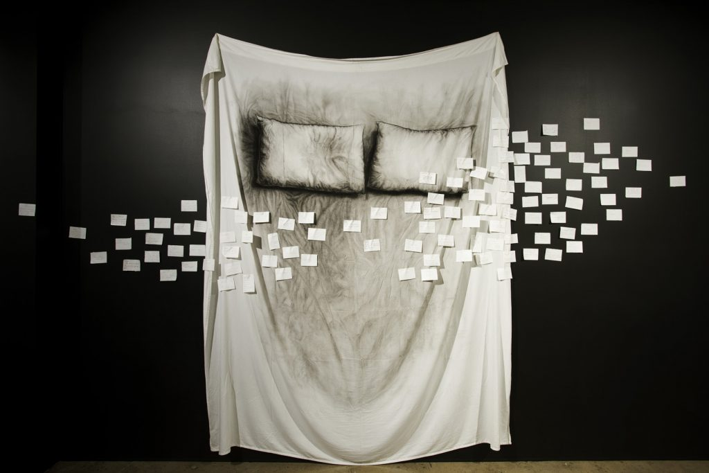 Margaret Ambridge, 'memories' Bed', Rice paper scribed by participants, pinned to charcoal on cotton queen size bed sheet,2600 x 2300 mm. Photography by Mark Fitz-Gerald.
