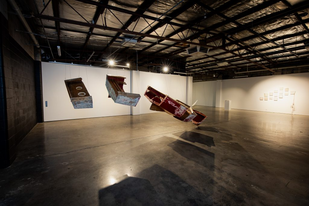 A suspended boat, deconstructed, in the gallery, along with Edwina Cooper's small works made of sailcloth.