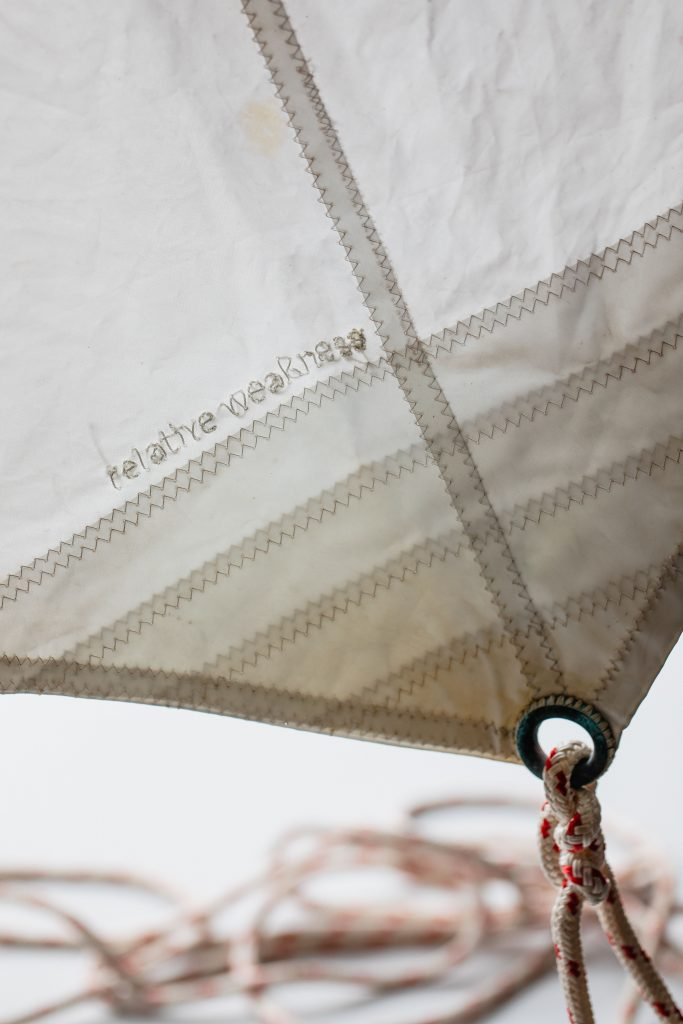 A close up detail of Edwina Cooper's small work 'relative weakness', depicting stitched sailcloth and the words 'relative weakness' sewn in, as well as training red cord.